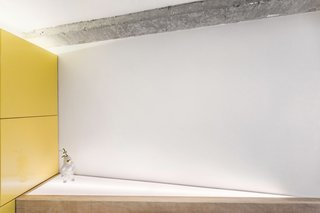 A triangular addition with a light box was inserted behind the sofa to align the living space with the angled TV wall.