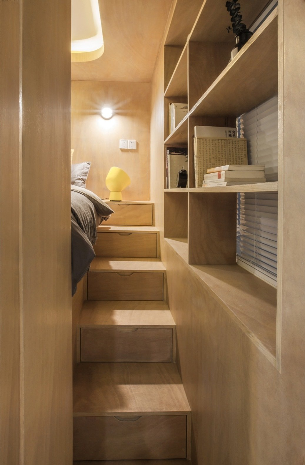 Bedroom, Shelves, Bed, Medium Hardwood Floor, Table Lighting, and Wall Lighting The second staircase is skinnier and sandwiched between the bed and window.    Photos from Rotated Volumes Cleverly Maximize Space in a Tiny Shanghai Apartment