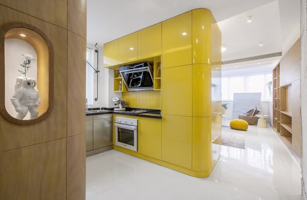 The centrally located kitchen volume is faced with high-gloss lacquered panels and features a yellow tile backsplash with black artificial stone countertops.