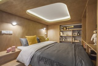 A look inside the cozy bedroom lined in wood veneer. A recessed skylight-inspired lighting feature helps keep the space from feeling too snug.