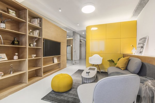 The living area has been carved out from the space between the yellow kitchen box and the wood-paneled entertainment box.