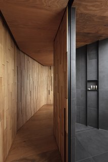 The bathroom features a spacious walk-in shower lined in charcoal porcelain tiles.
