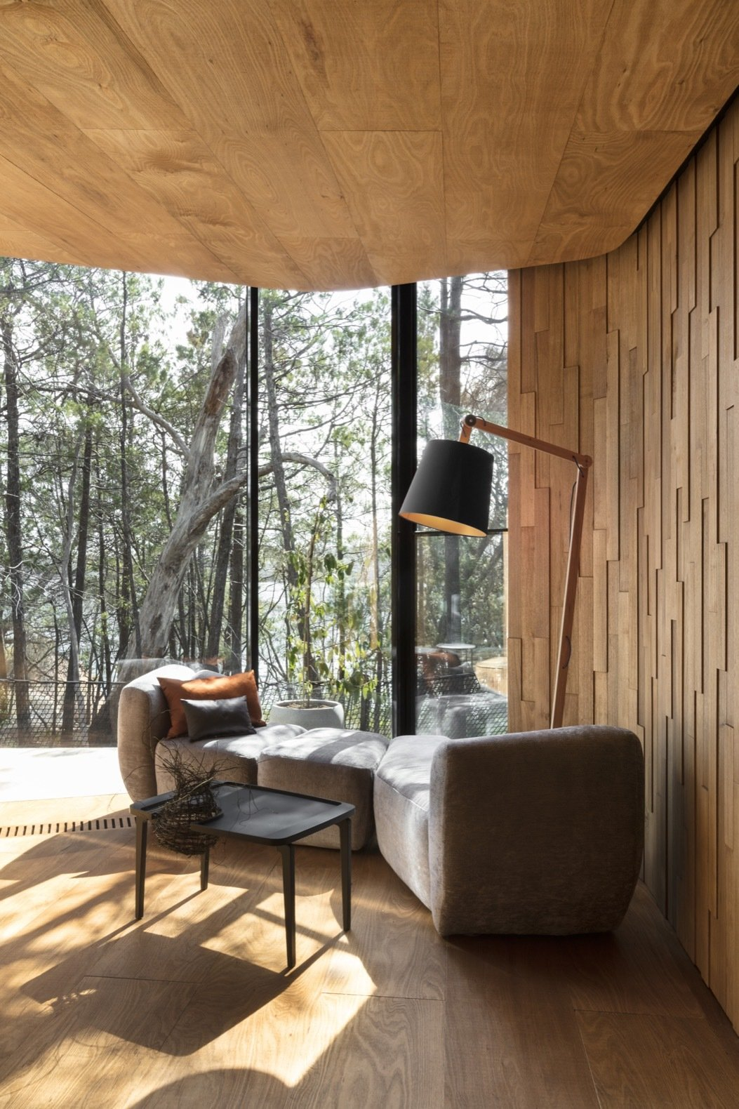 Living Room, Coffee Tables, Sofa, Light Hardwood Floor, and Floor Lighting The landscape-inspired interior features a simple color palette of grays, oranges, and blues.  Photo 5 of 13 in Escape to the Wilds of Tasmania in These Eco-Minded Pavilions