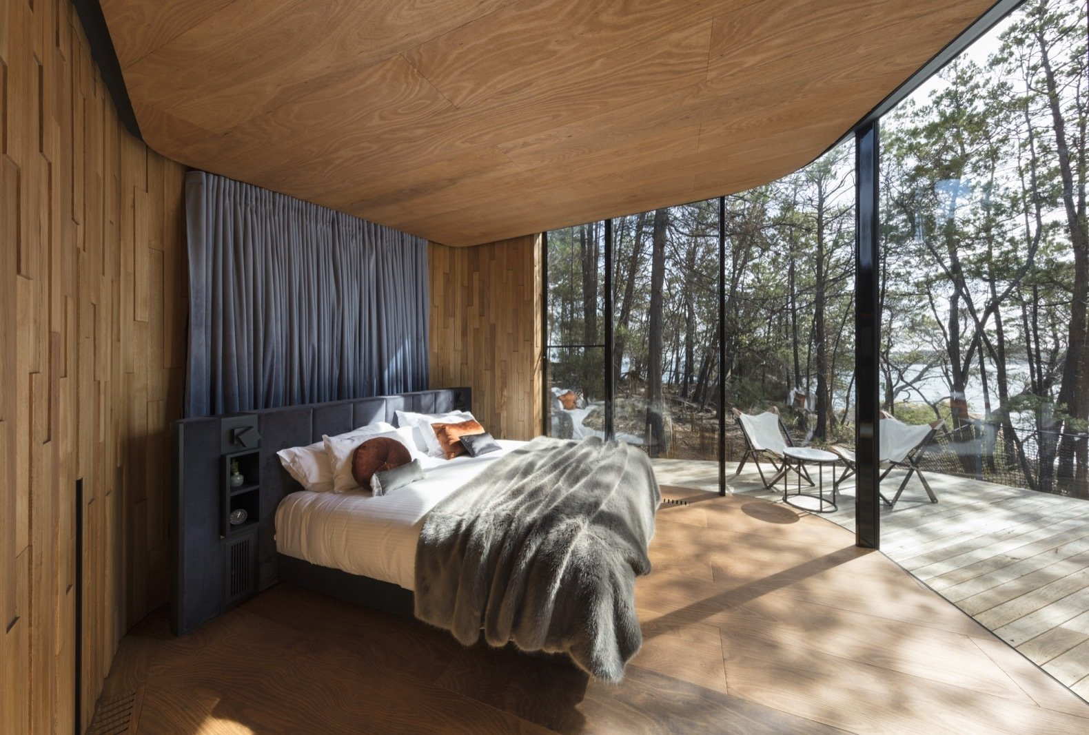 Bedroom, Light Hardwood Floor, Bed, and Night Stands Curved, full-height glazing erases the boundary between indoors and out.   Freycinet Lodge from Escape to the Wilds of Tasmania in These Eco-Minded Pavilions