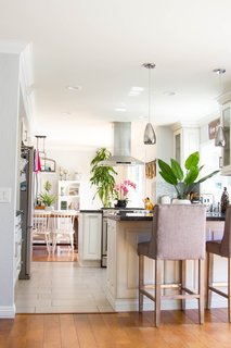The renovation created a lighter, more open atmosphere with views extending from the dining room through the kitchen and to the living space in the rear. To break up the rooms, the couple replaced the wood kitchen floors with staggered tile from Arizona Tile.