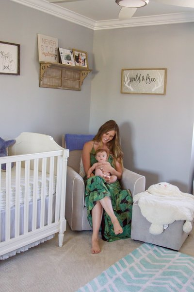 Janelle and her four-month-old son, Carter, relax in the nursery. All the wood paneling was removed, the walls and ceilings were repainted, and new carpet was put in.