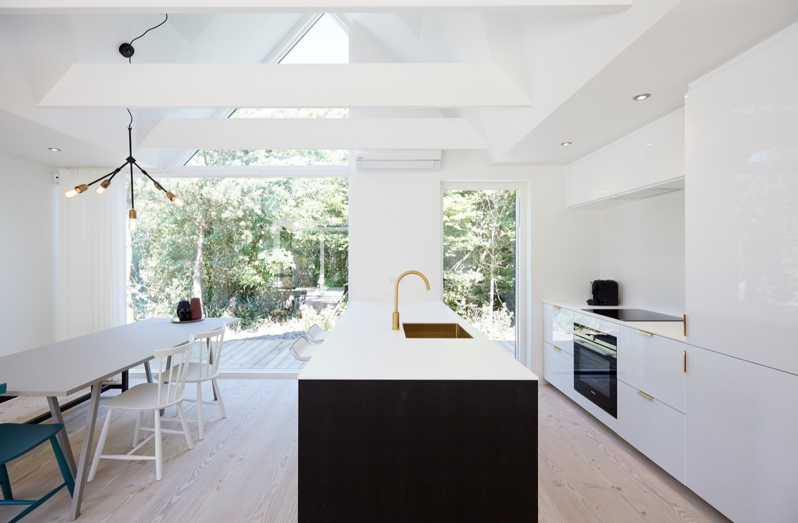 Kitchen, Recessed Lighting, White Cabinet, Pendant Lighting, Light Hardwood Floor, Refrigerator, Cooktops, Wall Oven, and Undermount Sink The kitchen is fitted with sleek metal hardware, high-gloss white cabinetry, and a spacious kitchen island that doubles as a breakfast counter.    Photos from Revel in Scandinavian Design at This Seaside Holiday Home