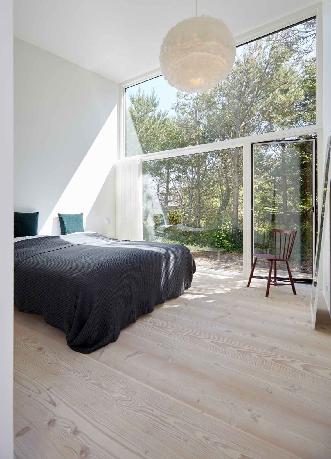 Bedroom, Bed, Chair, Pendant, Light Hardwood, and Table A 16-foot-tall wall of glass opens the master bedroom to views of the forest.   Best Bedroom Light Hardwood Pendant Photos from Revel in Scandinavian Design at This Seaside Holiday Home
