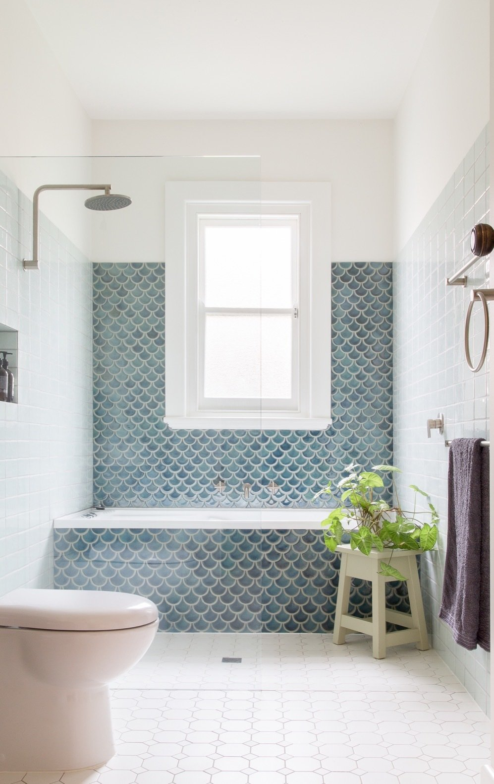 Bath Room, Two Piece Toilet, Porcelain Tile Floor, Stone Counter, Ceramic Tile Wall, Alcove Tub, Vessel Sink, and Enclosed Shower Handmade fish-scale tiles line the wall over the bath.  Best Photos from A Cramped Bungalow Is Reborn as an Eco-Minded Abode For Two Gardeners