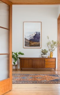 A view from the lounge into the converted study furnished with a vintage midcentury sideboard.