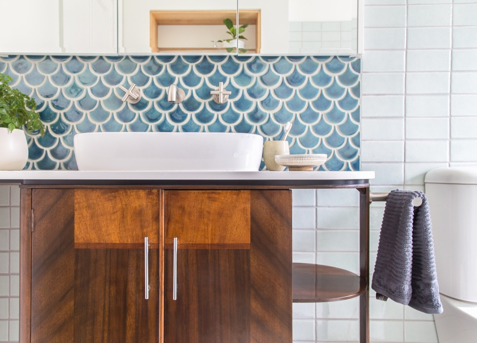 Bath Room, Stone Counter, Two Piece Toilet, Vessel Sink, and Ceramic Tile Wall An art deco drinks trolley was repurposed as a bathroom vanity. All fixtures are low-flow.   Photo 10 of 15 in A Cramped Bungalow Is Reborn as an Eco-Minded Abode For Two Gardeners