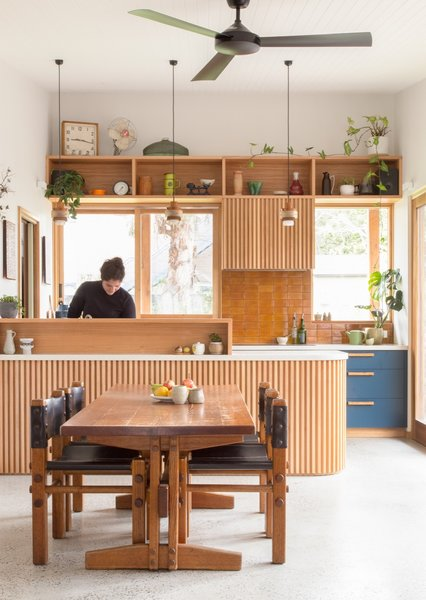 Recycled timbers are used throughout the home from the curved bench to the joinery in the kitchen. The kitchen also connects to a cold-store walk-in pantry that's cooled with an in-slab ventilation pipe funneling cool under-house air.