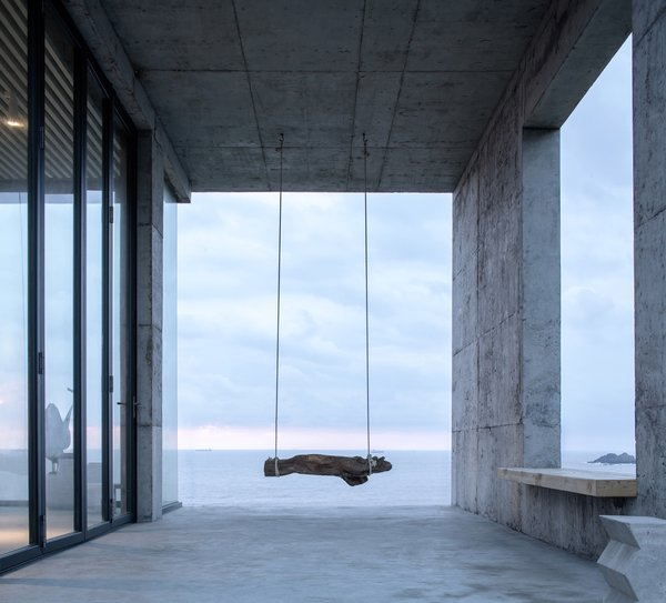A swing, fashioned from string and driftwood, hangs from the ceiling of new the concrete addition.