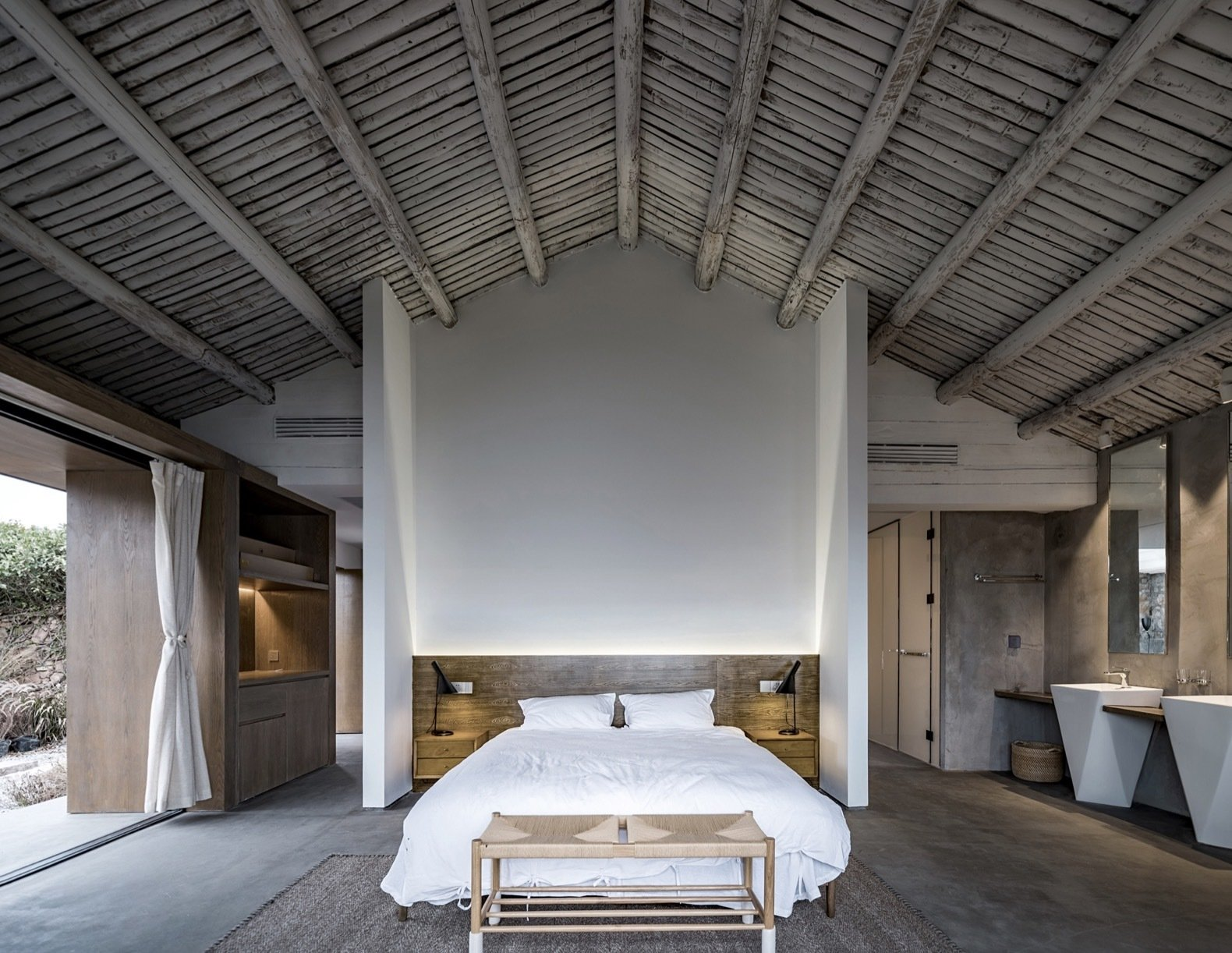 Bedroom, Concrete, Bed, Table, Night Stands, Storage, Rug, and Bench A timber beamed ceiling adds a rustic touch to the modern master suite.   Best Bedroom Bed Rug Concrete Bench Photos from In Just 31 Days, These Historic Chinese Ruins Were Transformed Into a Chic B&B