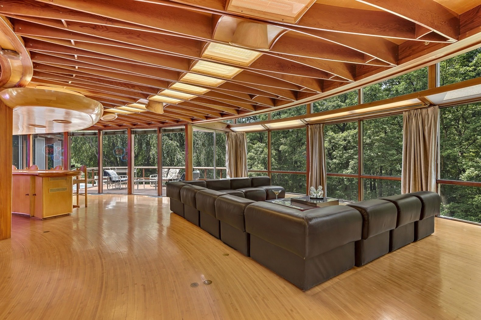 Living, Medium Hardwood, Bar, Recessed, Sofa, Stools, and Coffee Tables Full-height glazing wraps around the home for spectacular views of the woods.   Living Medium Hardwood Recessed Bar Photos from Jackie Gleason's Spaceship-Like Mansion Hits the Market For $12M