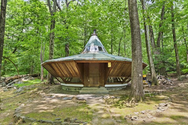 "Nicknamed ""The Spaceship,"" the small UFO-inspired cottage includes a tiny utility kitchen, bathroom, and storage."
