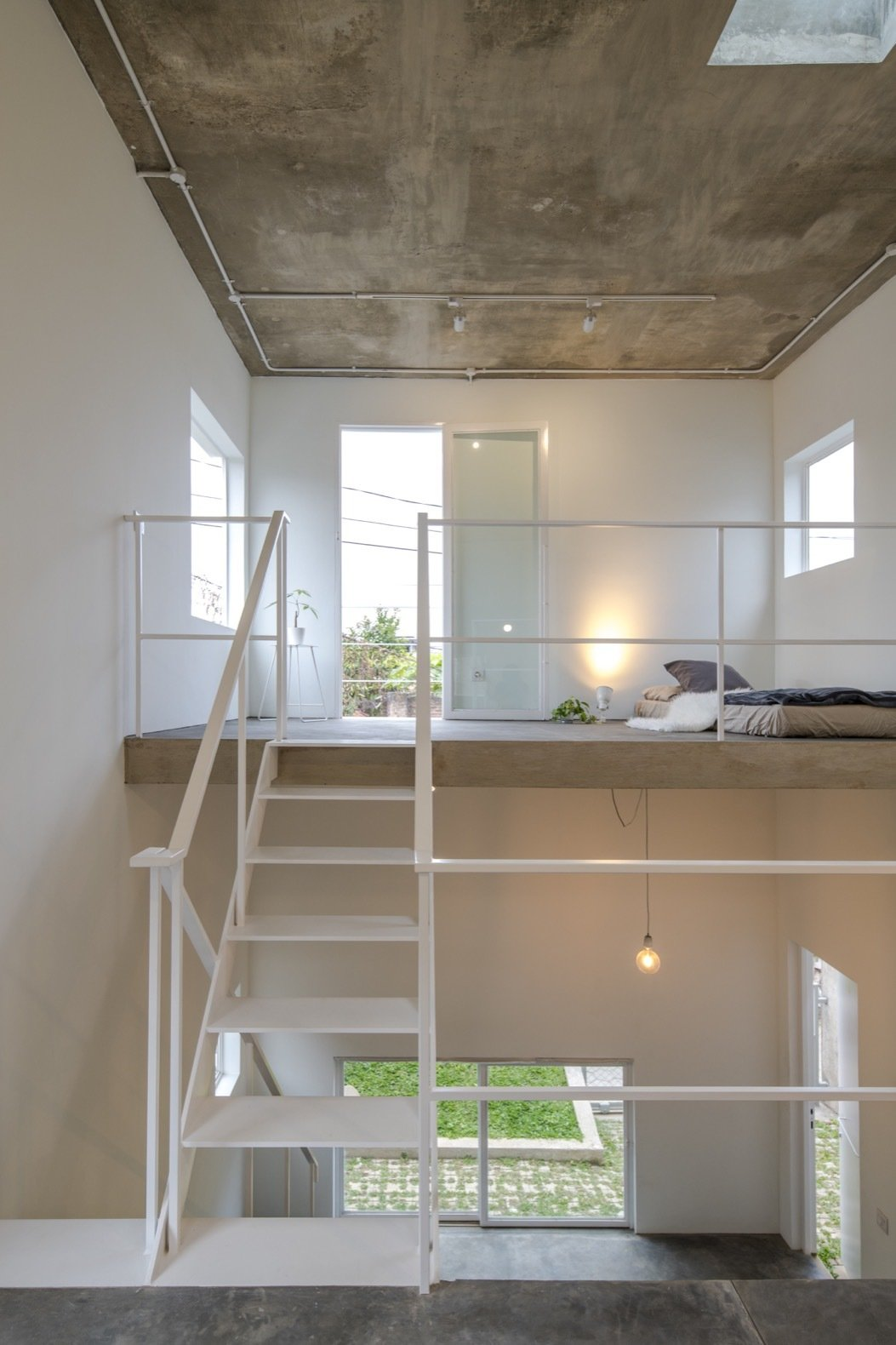 Bedroom, Bed, Pendant Lighting, Concrete Floor, Ceiling Lighting, and Table Lighting The bedroom is located on the uppermost level that connects to a small outdoor balcony.    Best Photos from This Skinny, Minimalist Home Gets a Modern Revamp For $20K