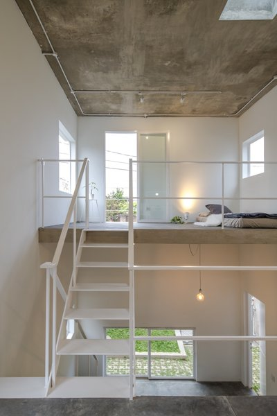 The bedroom is located on the uppermost level that connects to a small outdoor balcony.