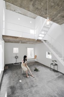 The floors are built of exposed concrete, while the brick walls have been painted white.