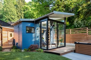Blue-painted cedar siding wraps around the 169-square-foot Backyard Reading Retreat. The smaller wooden shed hidden in the rear houses a prefab dry sauna.