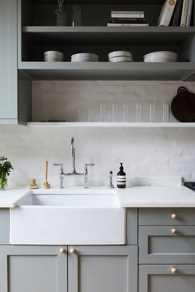 The kitchen countertops and shallow shelf are Olympian White Danby marble. The white oak cabinet knobs are from Etsy.