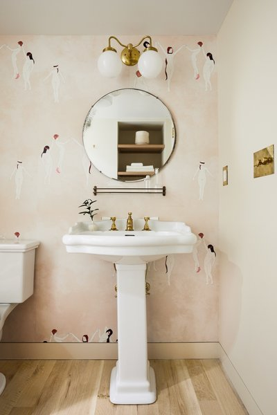 The Garden Bathroom serves as the powder room and the guest bathroom. The Maison C via Studio Four wallpaper complements the Benjamin Moore Bone White-painted walls.