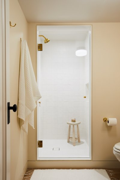 The shower is lined with matte white squares with an irregular, handmade feel, Matte white square penny tiles are used for the shower floor.