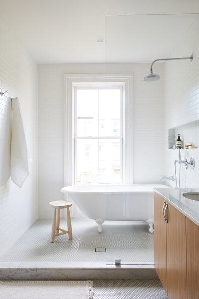 A clawfoot tub was installed beneath the window and can be seen from the bedroom. The semi-enclosed shower room is lined in white subway tile while sage green penny tiles cover the floors.