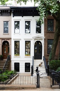 The original brownstone exterior was given a bright refresh with Farrow & Ball Skimming Stone paint on the facade and Benjamin Moore Black for the trim, door, balusters, and handrails. The architectural designers also added new windows and doors.