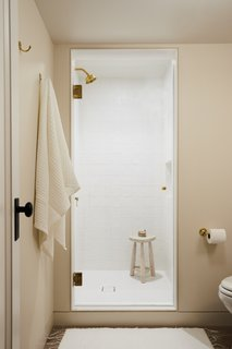 The shower is lined with matte white squares with an irregular, handmade feel. Matte white square penny tiles are used for the shower floor.