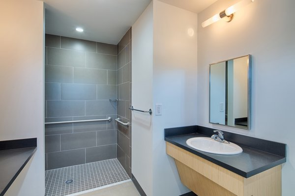 One of the two bathrooms is ADA-compliant and features Trinity Tile Cement Tech 12 x 24 tiles and Formica plastic laminate counters.