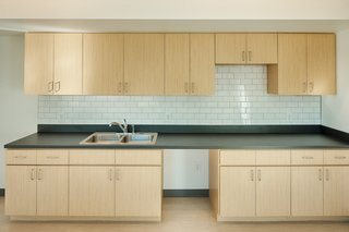 The kitchen features a Trinity Tile backsplash as well as Formica plastic laminate counters and cabinets.