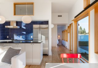 The Open Kitchen Is Fitted With Black Granite Counters A Ceramic Backsplash And Melamine