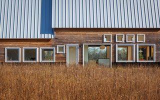 Galvalume standing metal seam roofs reflect the sunlight, while horizontal planks of natural cedar siding are left untreated to weather.