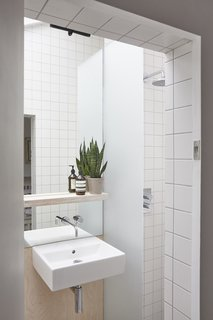 A peek inside the bathroom. This space is lined with matte white tiles and pale gray grout.