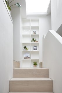 The stairs, built of white-stained engineered oak, connect the lower-level living area with the kitchen and bedrooms.