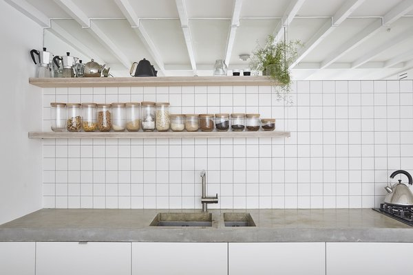 A high-level mirror above the white-tile backsplash reflects the deliberately exposed ceiling joists, while also visually extending the space.