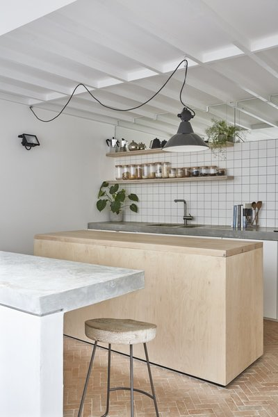 Bert & May Terracotta Arcilla handmade tiles line the kitchen floor and are complemented by cabinets with IKEA carcasses and white-sprayed MDF doors. There is also a cast in-situ concrete counter, which can be used as a secondary dining area or breakfast bar.
