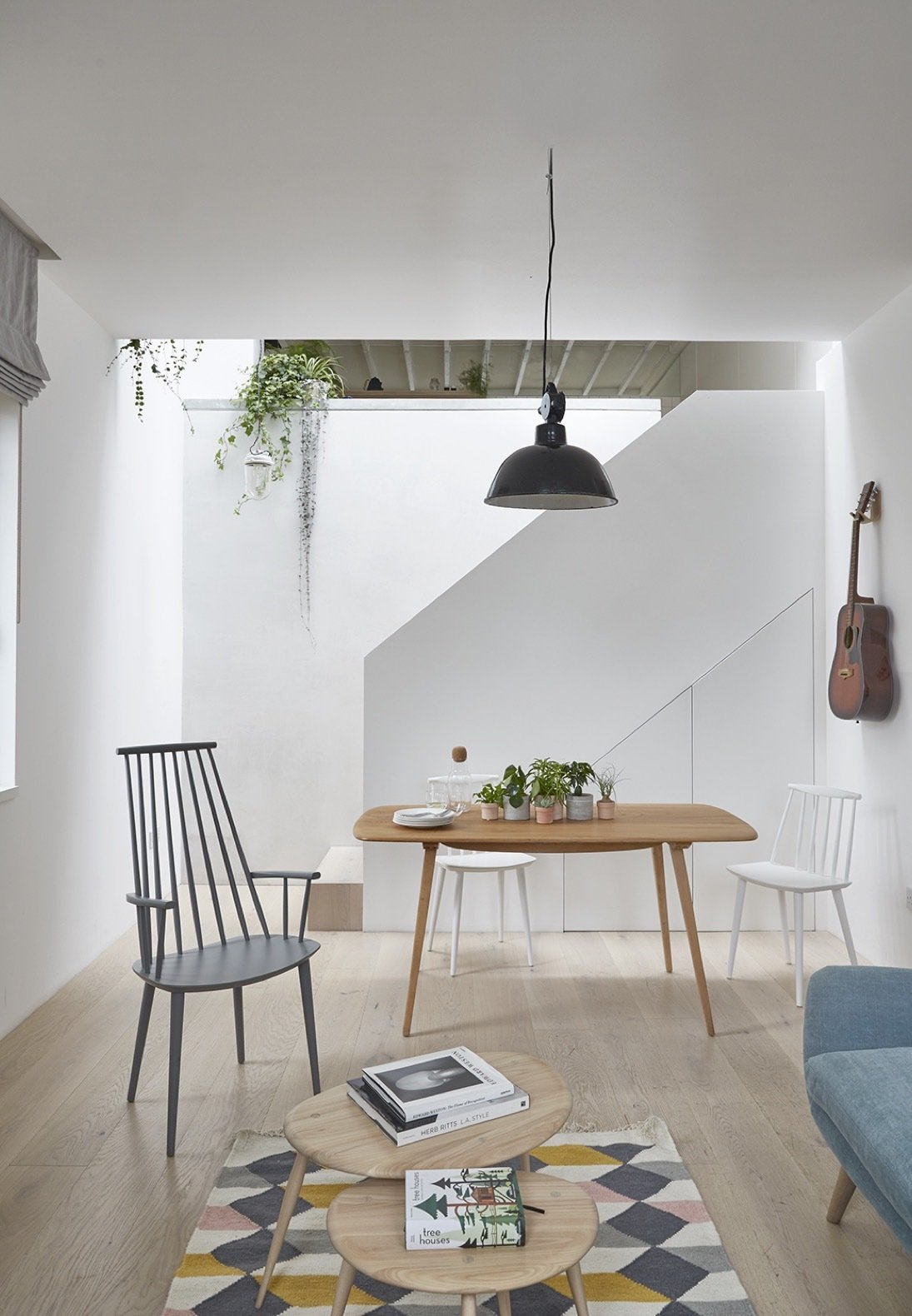 Living Room, Chair, Pendant Lighting, Table, Coffee Tables, Sofa, Light Hardwood Floor, and Rug Floor The dining and coffee tables are from Ercol. The chairs are from HAY.    Photo 3 of 13 in A Claustrophobic London Mews House Gets a Smart Redesign