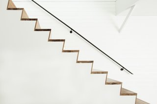 The elegant walnut steps are paired with a railing made of natural, hot-roll steel.