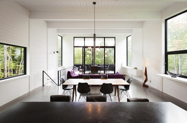 Polished concrete floors with integrated radiant heating are used throughout the home, while the walls are lined with white-painted wood planks.