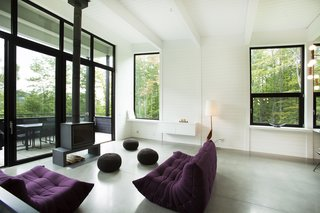 The living room is anchored by a wood-burning stove. The sofas in this room are by Ligne Roset.