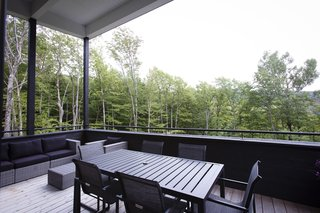 Untreated-timber floor planks provide contrast against the black-painted elements and furnishings in the covered patio.