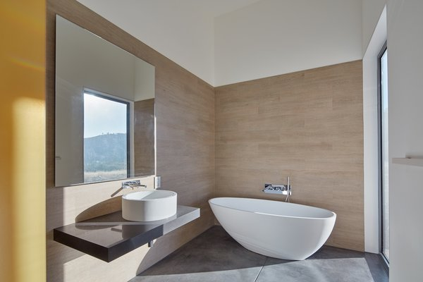 The guest bedroom features a soaking tub with a full-height window overlooking the deck and landscape beyond.