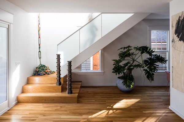 The new staircase was installed next to old windows on the east wall, and ascends to a light-filled hall above.