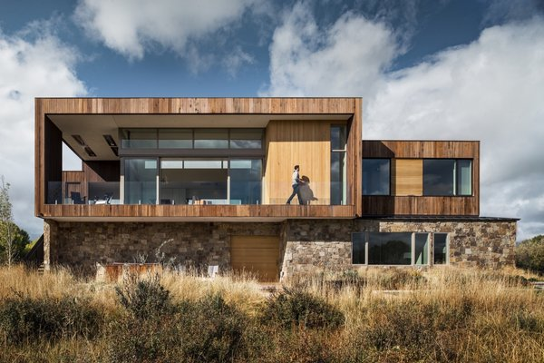 Rising out of the earth like a natural rock outcropping, the holiday retreat is clad in a combination of stained Western Red Cedar and stained Alaskan Yellow Cedar on the upper volume, while the lower is wrapped in stone veneer.