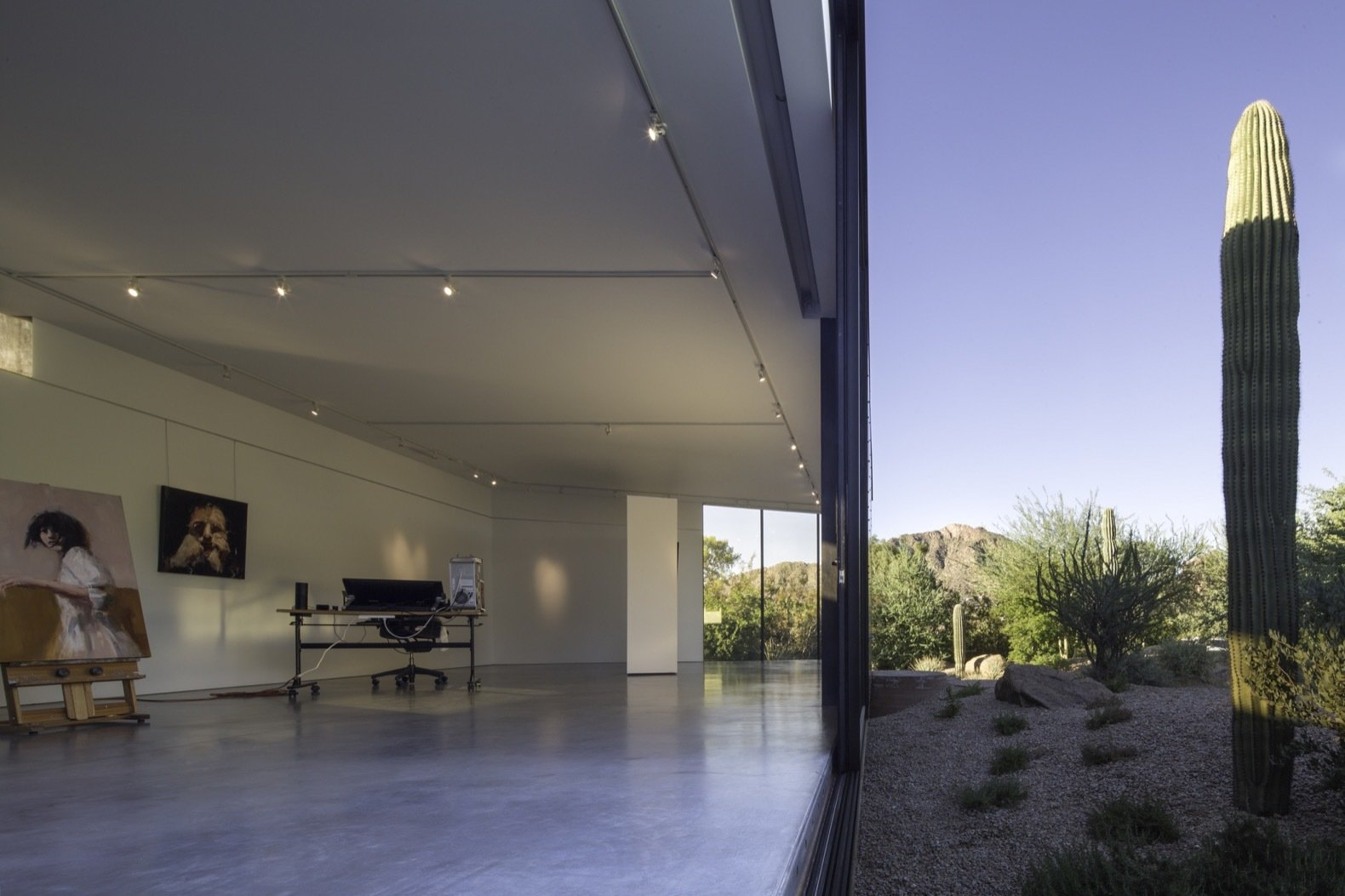 Doors, Exterior, Metal, and Sliding Door Type Set on sliders, the full-height glazed doors open up to seamlessly connect the art studio with the outdoors.    Best Photos from An Art Studio With Mirror-Like Glazing Floats Over a Desert Wash