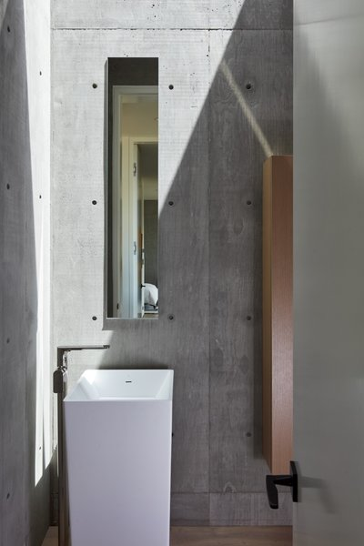 The powder room is framed with concrete walls and white oak floors, and is illuminated by a large skylight.