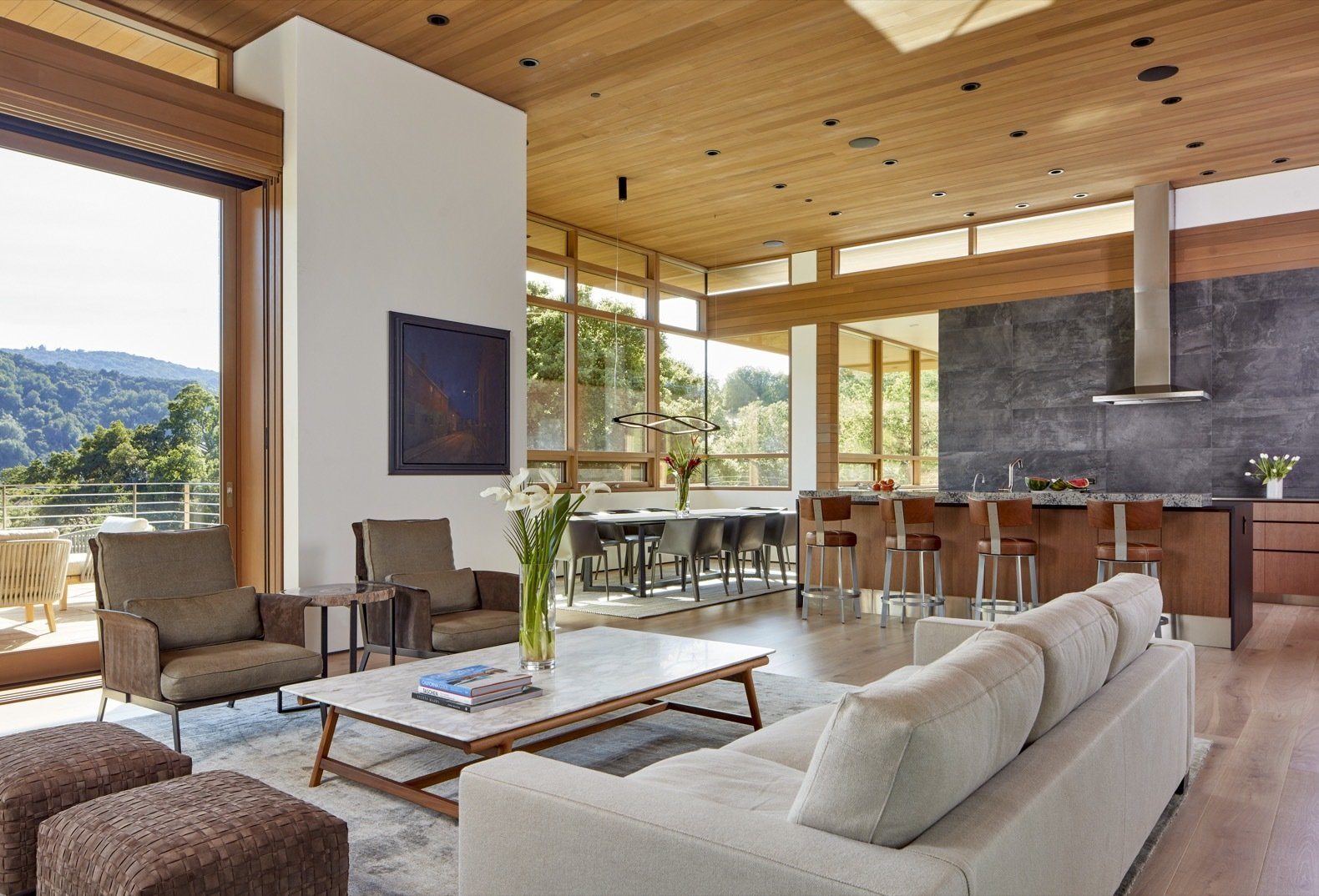 Living, Coffee Tables, Sofa, Chair, Medium Hardwood, Recessed, Table, Rug, Pendant, Stools, and Bar A soaring ceiling delivers a sense of drama to the open-plan great room.   Best Living Coffee Tables Pendant Recessed Chair Photos from A Californian Home Gently Steps Down on an Oak-Studded Landscape
