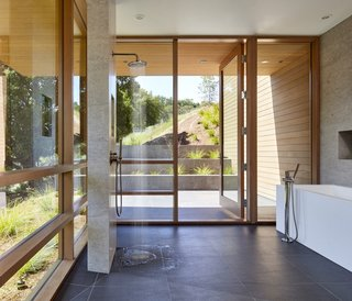 Shielded from the sun by large overhangs, the master bath is wrapped in full-height glazing. The porcelain tile floors are from Porcelanosa, and the walls are a mix of Western Red Cedar, tile, and painted gypsum.